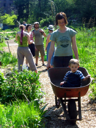 woman and child in wheelbarrow in community garden